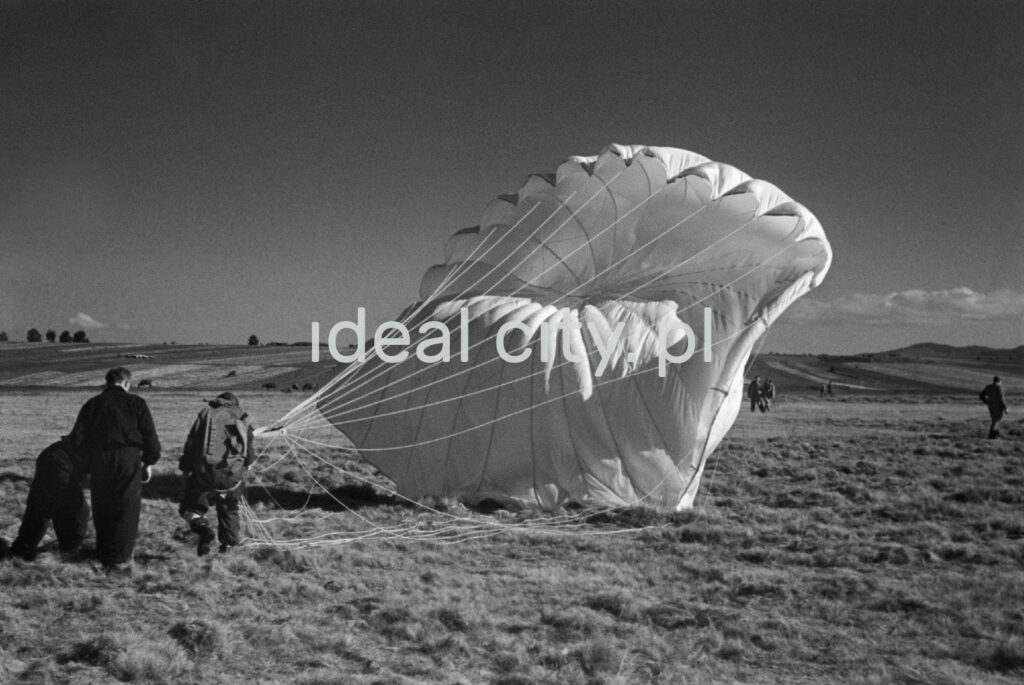 The paratrooper is standing on the ground with the parachute canopy spread out behind him.