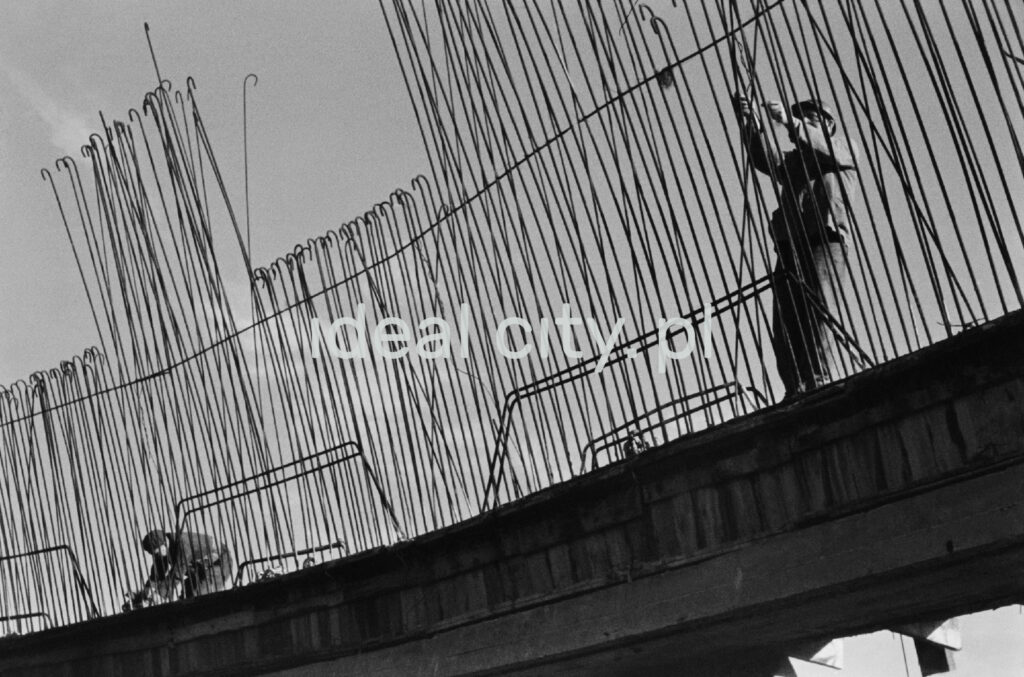 Workers assemble reinforcing wires that form a slightly sloping wall.