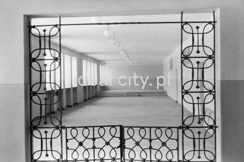 View through a window-sized opening in a patterned steel grille onto the school corridor.