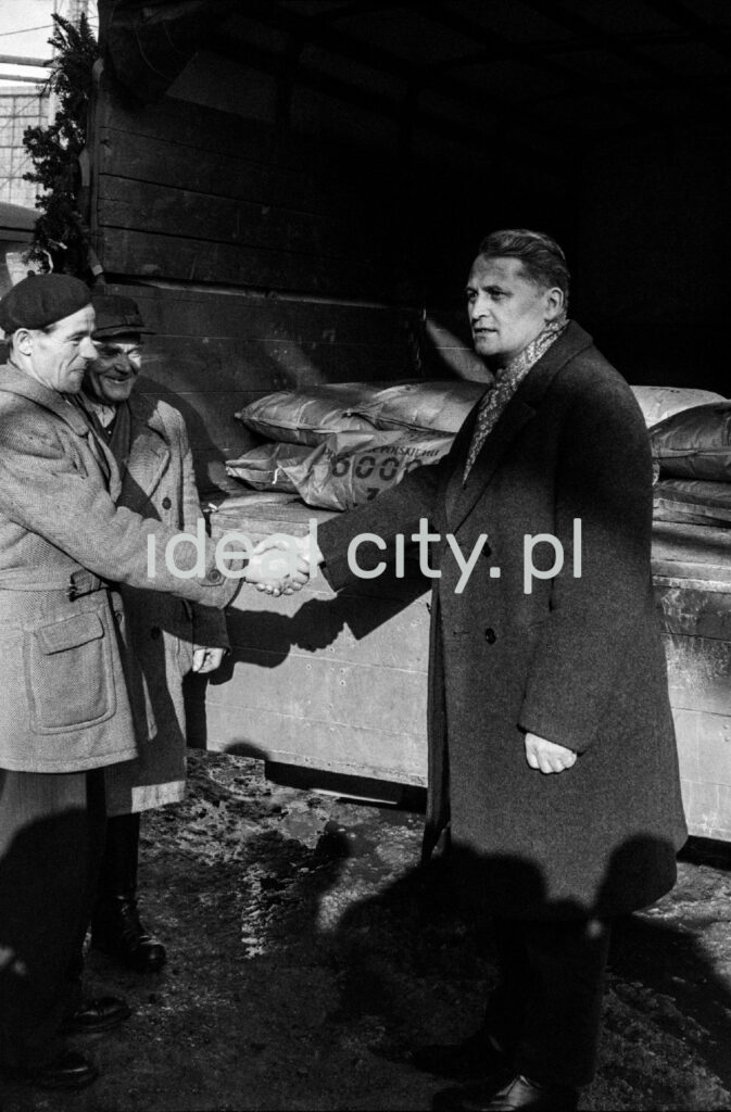 A man in a coat and a scarf shakes hands with those dressed in work clothes and a beret.