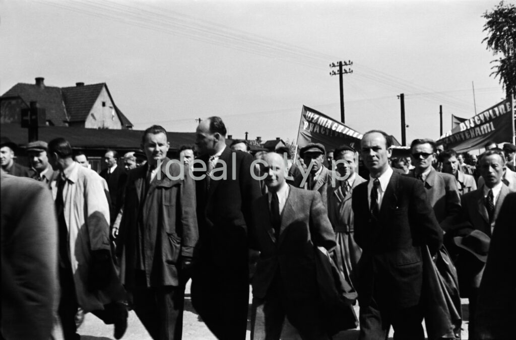 A group of men in official clothes marches forward dynamically, behind them a visible fragment of a banner with an illegible inscription.