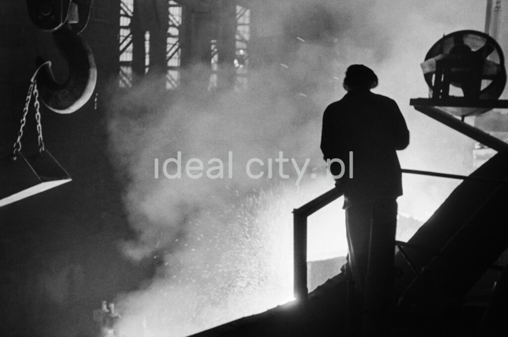 The silhouette of a man in work clothes watching from the platform, the embers puffing from the vat.