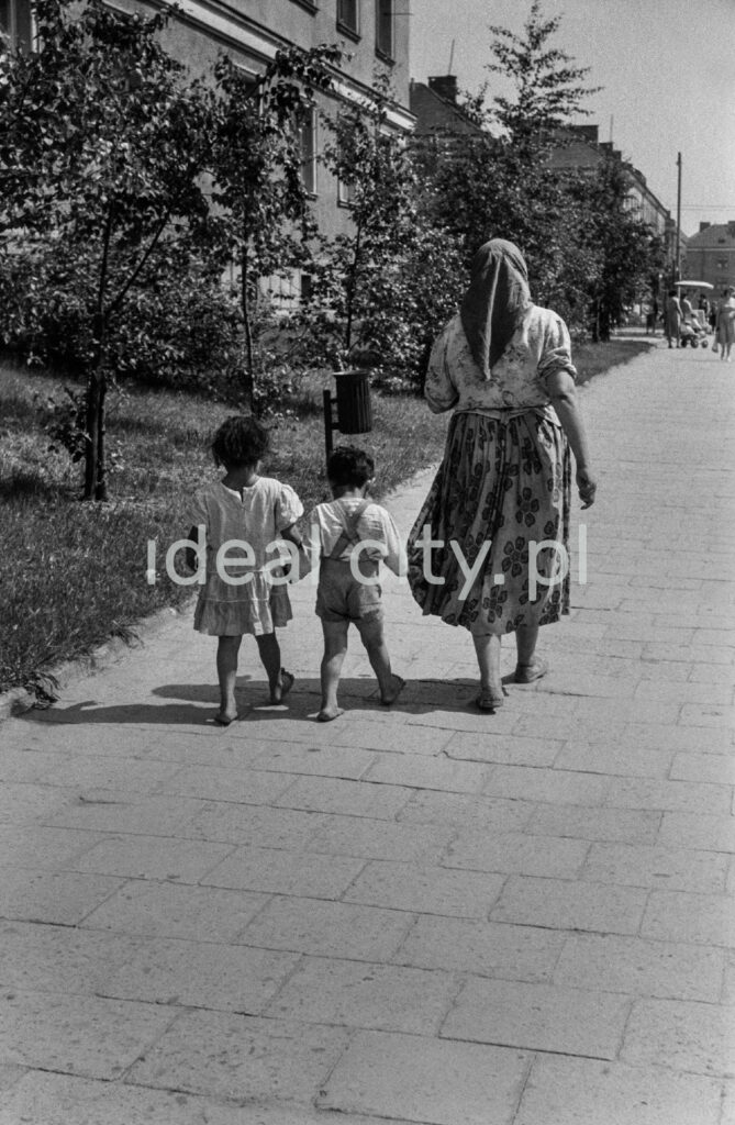 A woman in a patterned skirt and a headscarf walks barefoot along the pavement holding two children by the hand.