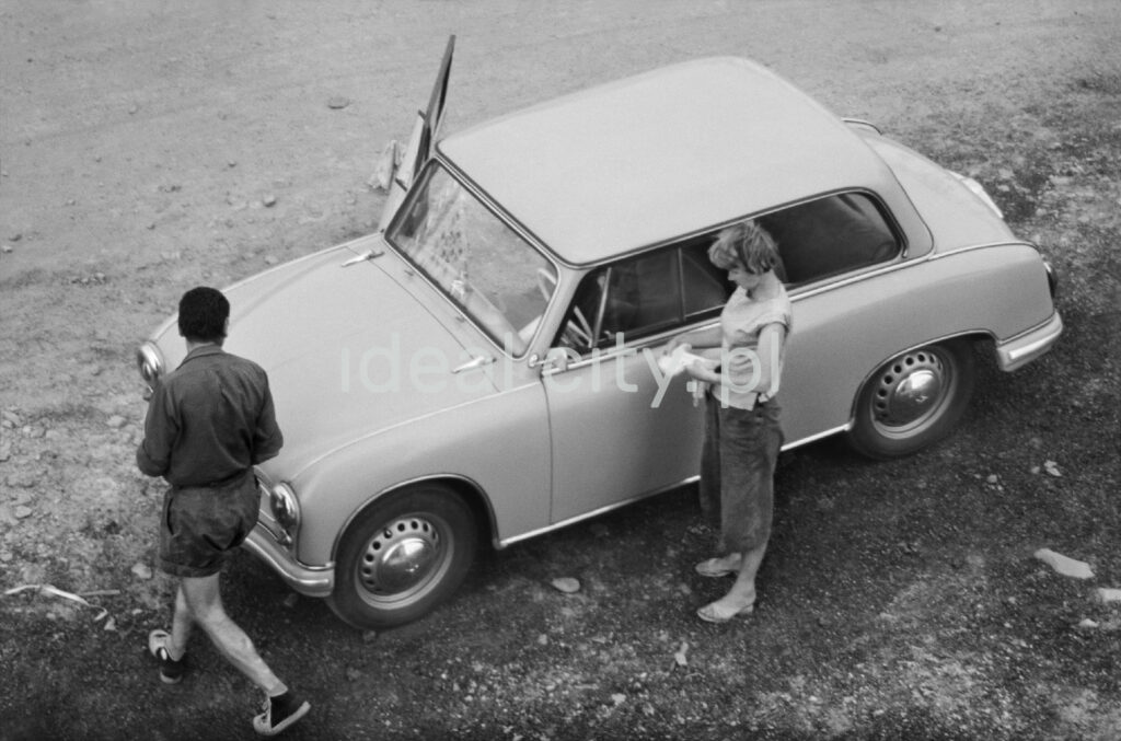 A view from the window of the first floor to a small car around which a woman and a man bustle.