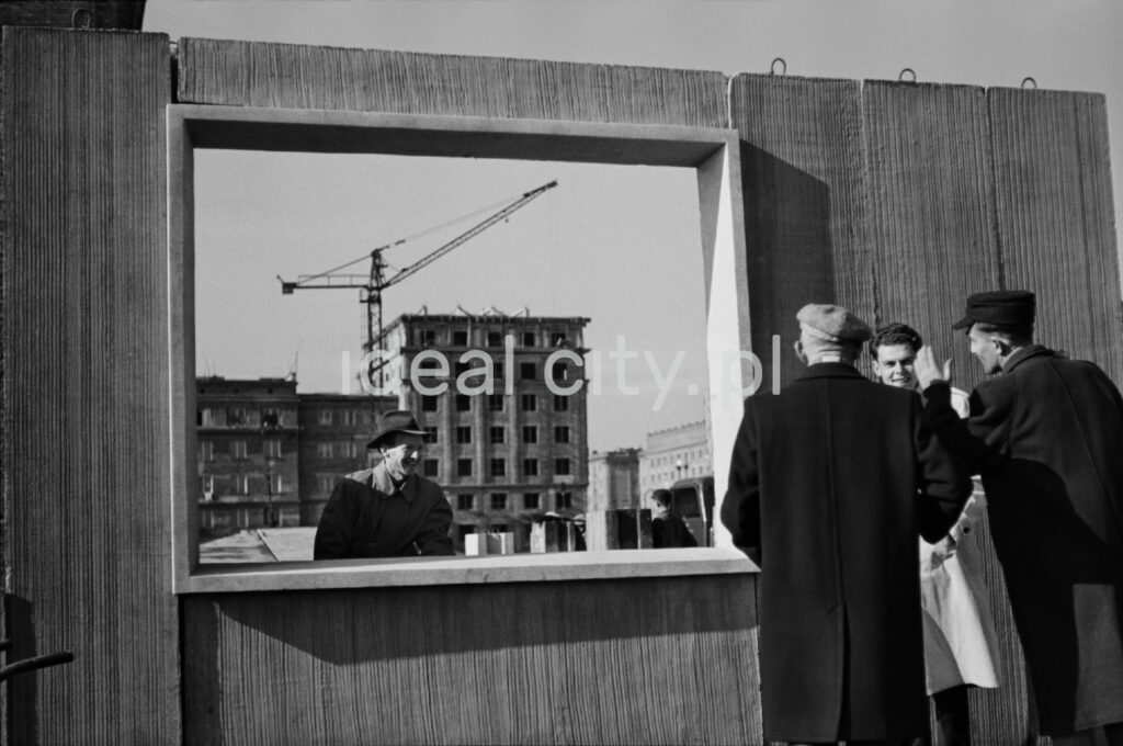 Four men are looking at a prefabricated wall from both sides with a window in the center through which a housing estate under construction and a crane can be seen in perspective.