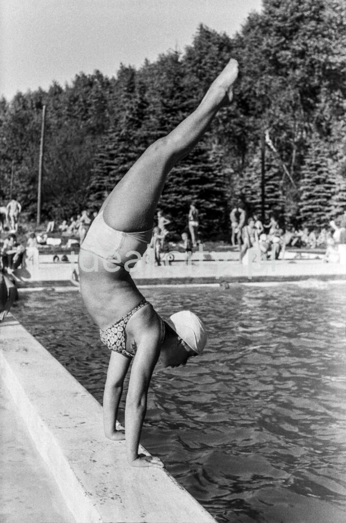 A gymnast in a swimsuit leans back on her hands into the pool.