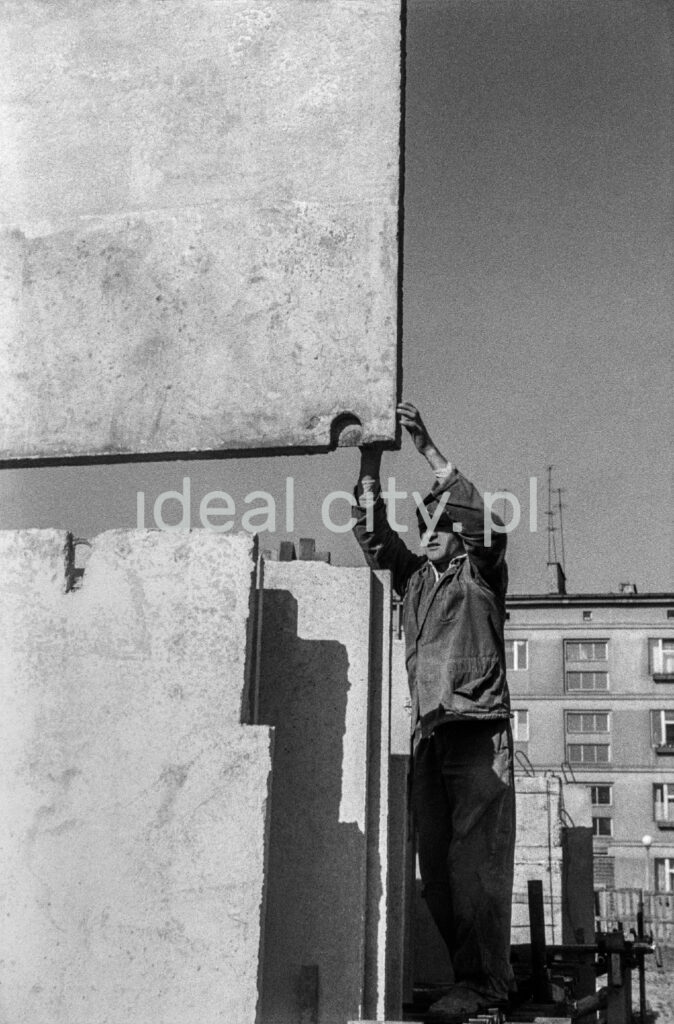 A man in work clothes and a beret on his head directs a prefabricated concrete slab fed to him by a crane.