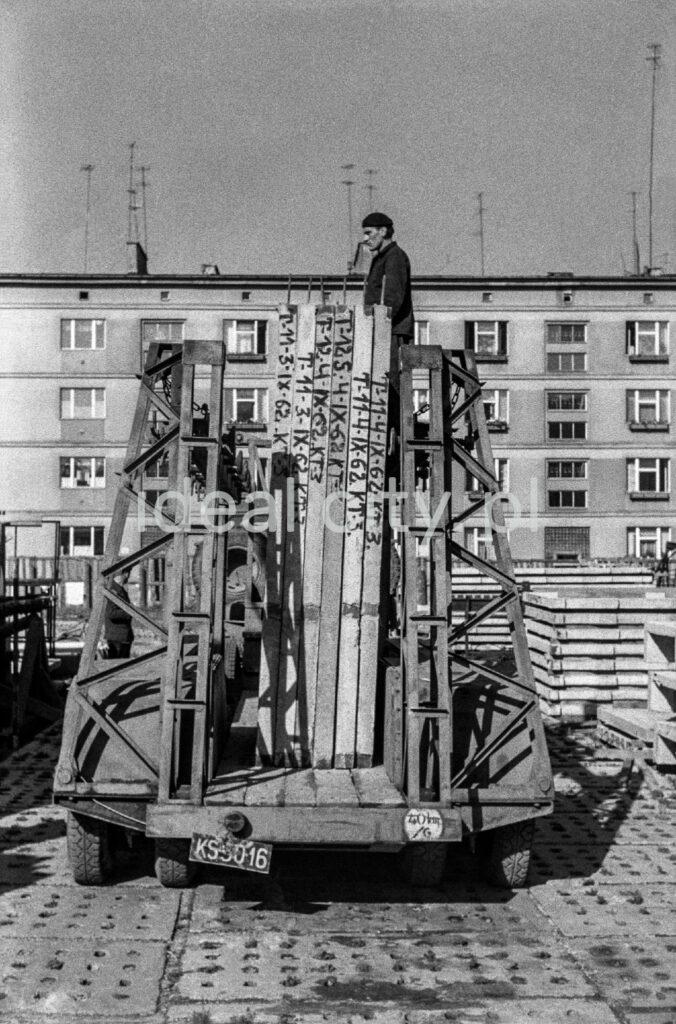 A man in overalls and a beret on his head is standing over prefabricated concrete slabs. An apartment block in the background.
