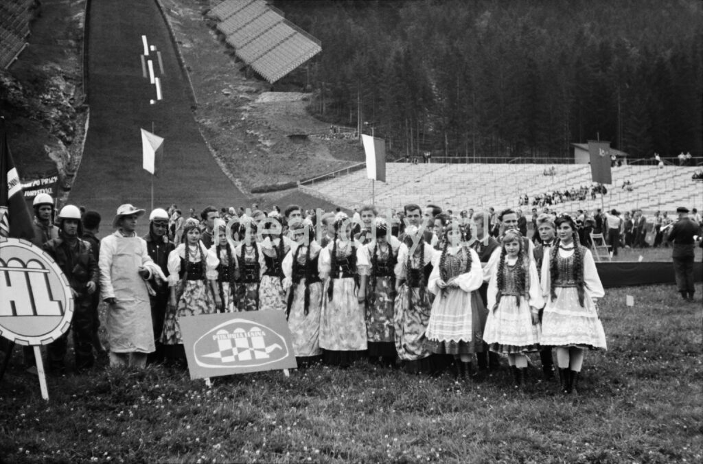A group of women in regional costumes and a few steelworkers in working clothes are posing in front of the ski jump.