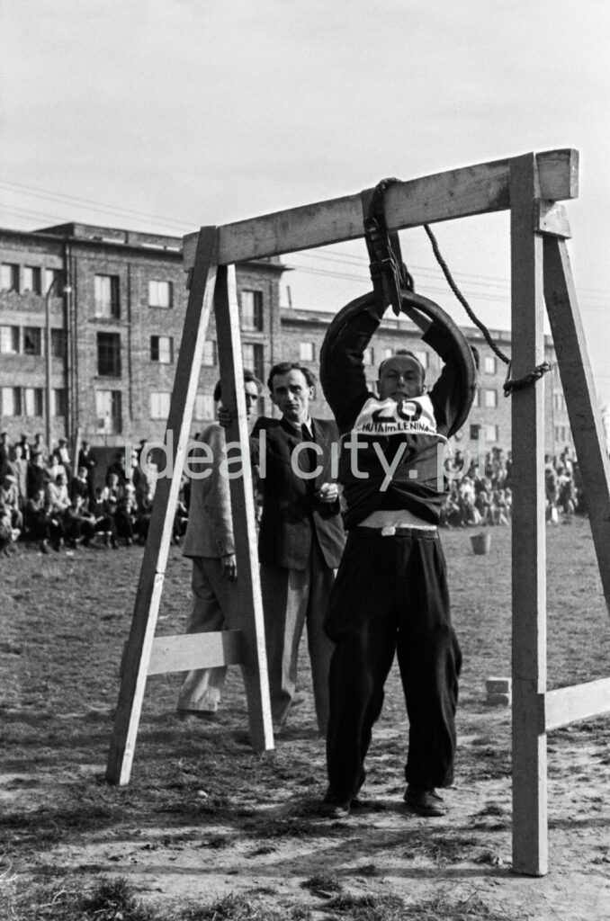 A man with the participant's number on his chest squeezes through a tire suspended on a wooden structure.