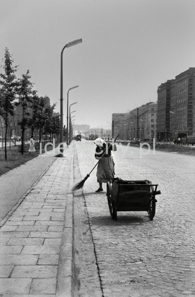 A woman with a broom in her hand and a scarf on her head is sweeping the street.