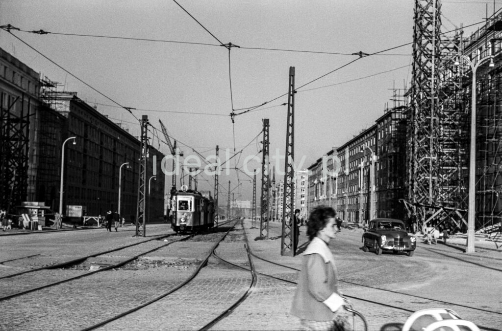 A woman with a pram is crossing the track with a tram in the background.