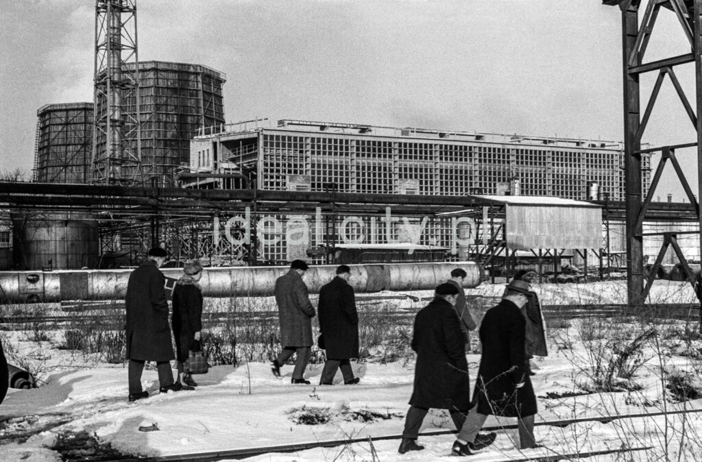 A group of men in coats and hats march through a snowy industrial area.