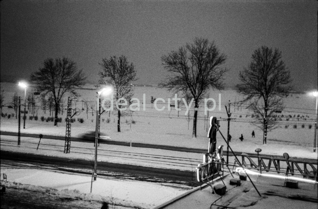 Winter view from the window on the road covered with snow, tram tracks, in the foreground a fragment of a neon sign above the one-story pavilion.