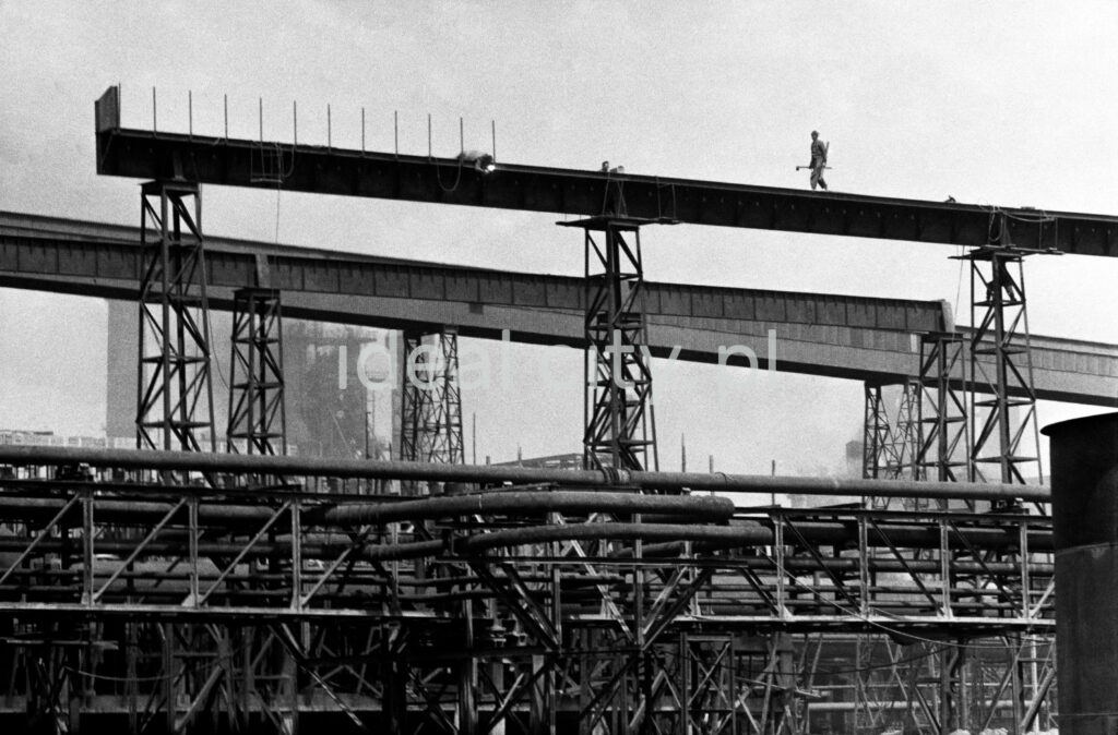 A view of the openwork structure of the factory, a man in work clothes with a long tool in his hand is walking upstairs.