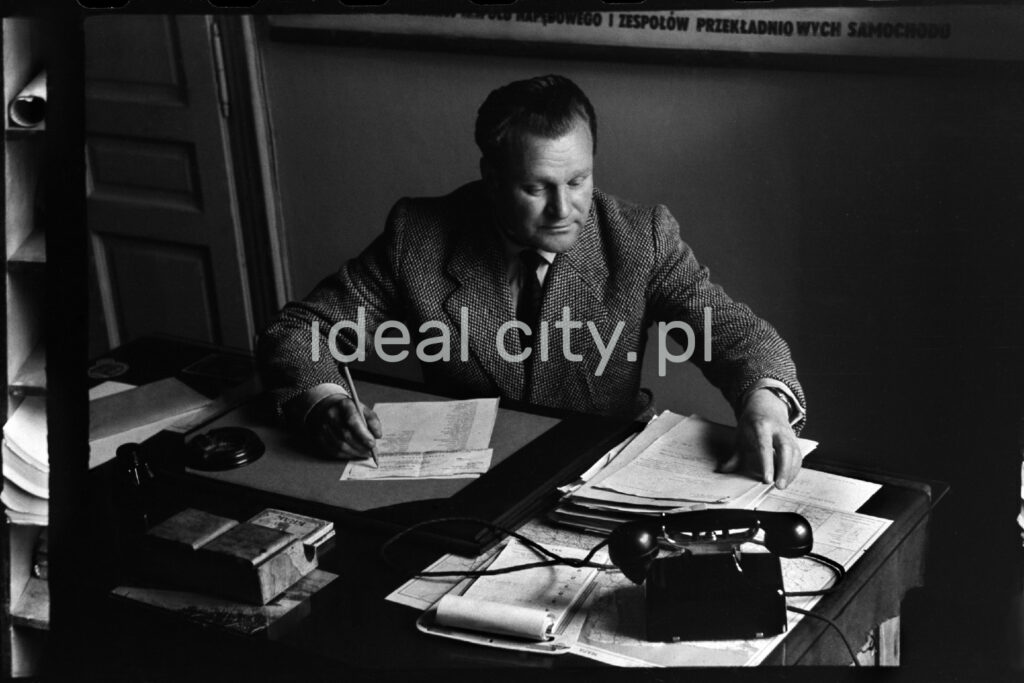 A man in a jacket is writing something while sitting at a desk.