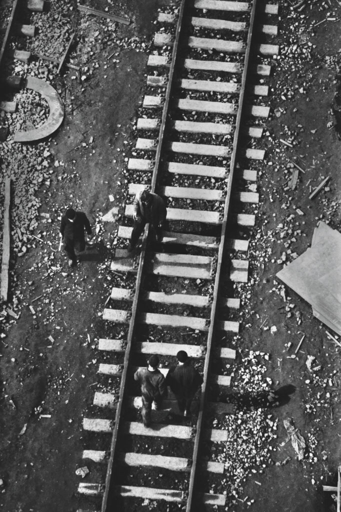 A view from a height of the railway tracks along which figures in working clothes are walking