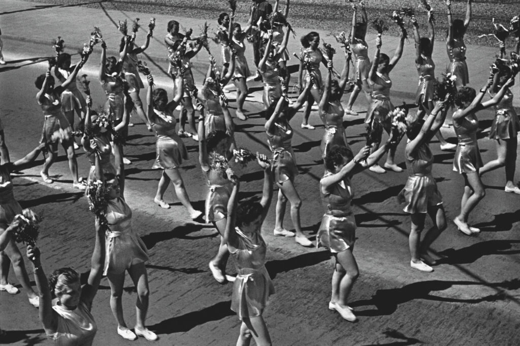 Top view of young women in sports clothes marching down a wide avenue with arms raised.