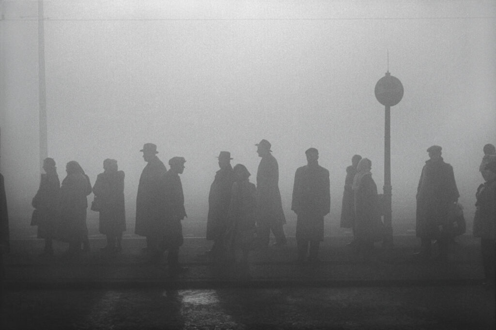 The contours of a group of people in coats and hats stand in the fog at the tram stop.