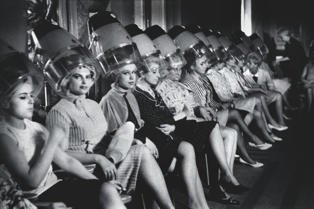 The women sit in a row under the hair dryers.