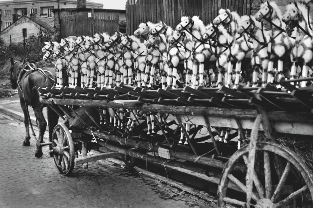 A row of wooden rocking horses lined up in a row on a wooden horse-drawn cart.