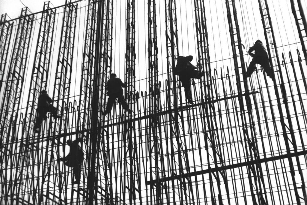 Five men in work coveralls assemble an openwork structure made of rebar at a height.