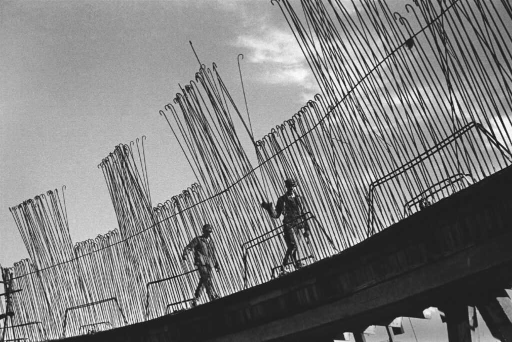 Two men in working clothes are walking at height along the lines of arms, the first of them runs his hand along them.