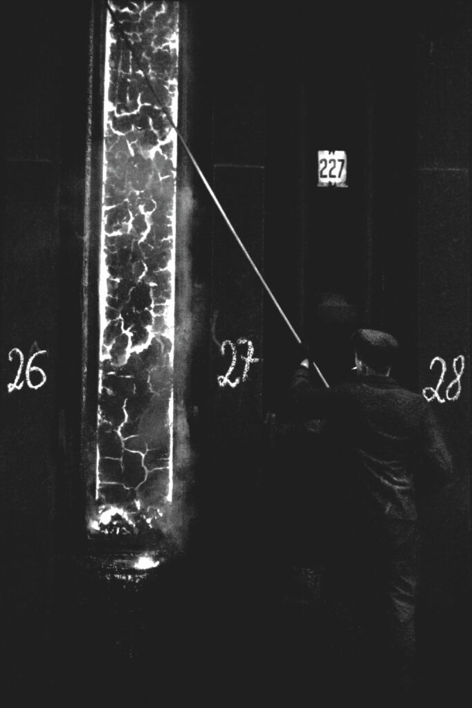 The steelworker adjusts the incandescent coke with a steel rod, visible in the isthmus of the wall of a huge, vertical structure.