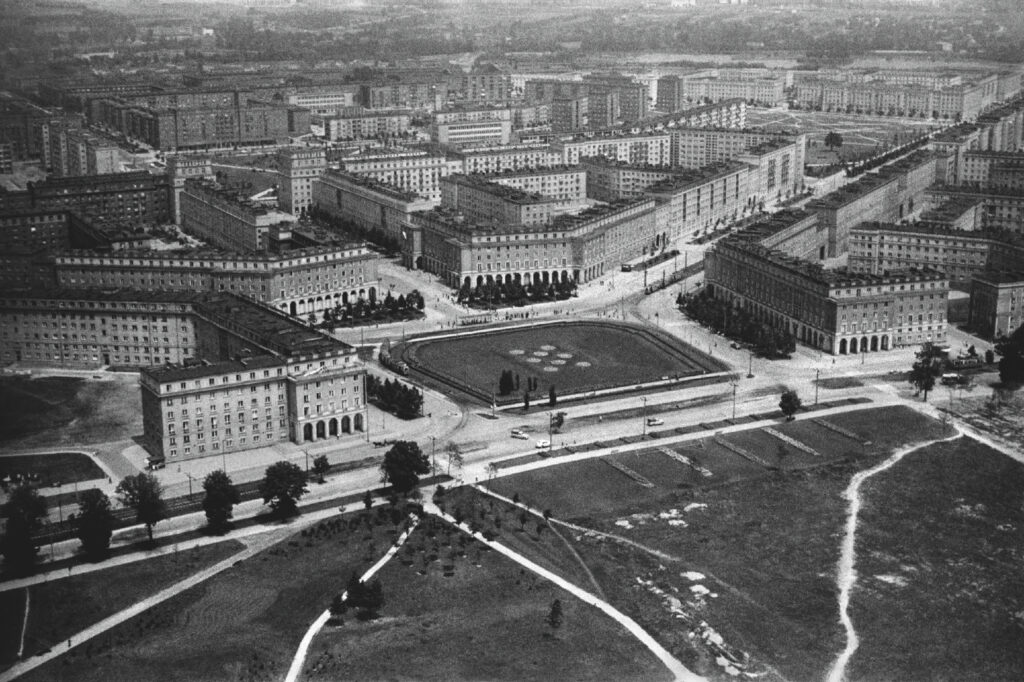 A bird's-eye view of the city square surrounded by monumental residential buildings, from which streets radiate.