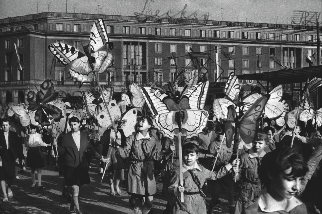 Children march in a procession carrying butterflies cut out of cardboard on sticks. Monumental residential buildings in the background.