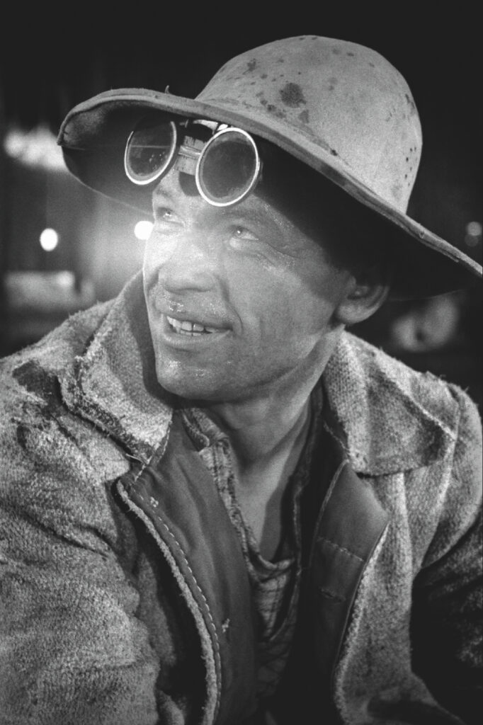 Portrait of a smiling steelworker in a work hat and goggles on his forehead looking up.