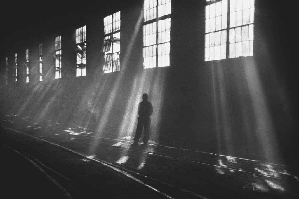A man in denim stands in the center of a dark hall, into which rays of sunlight fall from the windows above.