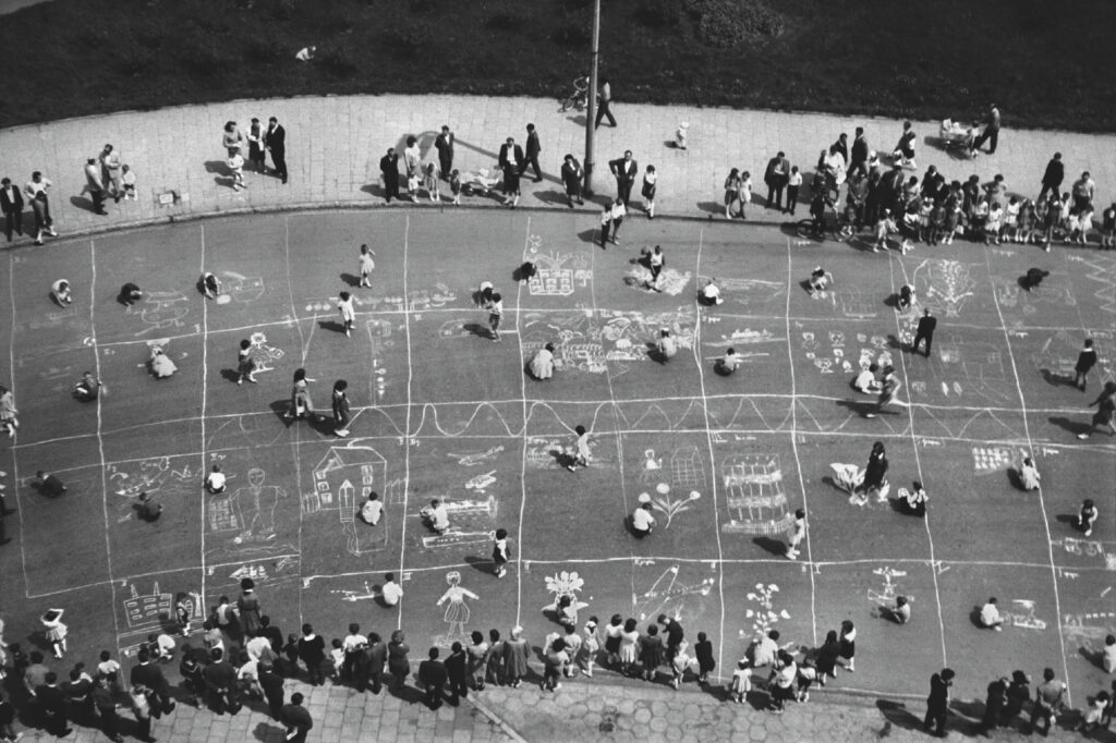 Top view of kids drawing houses and chimneys on the road with chalk.