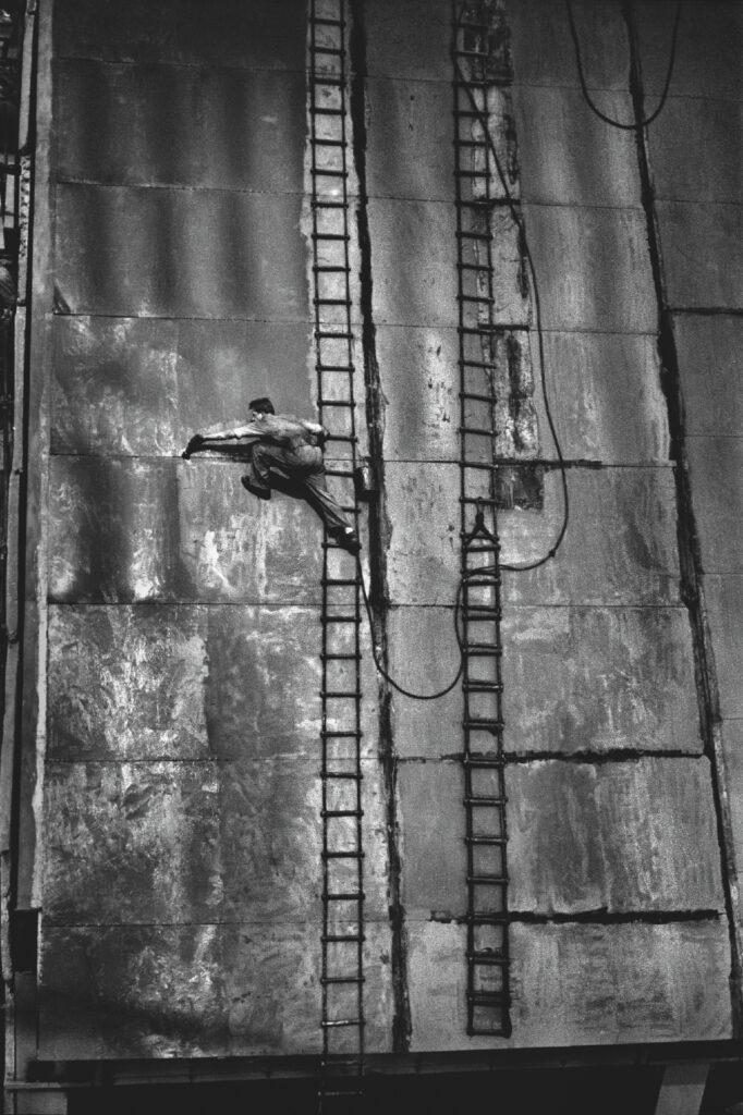 A man in work clothes lances out of a high ladder placed on the wall of a massive structure.