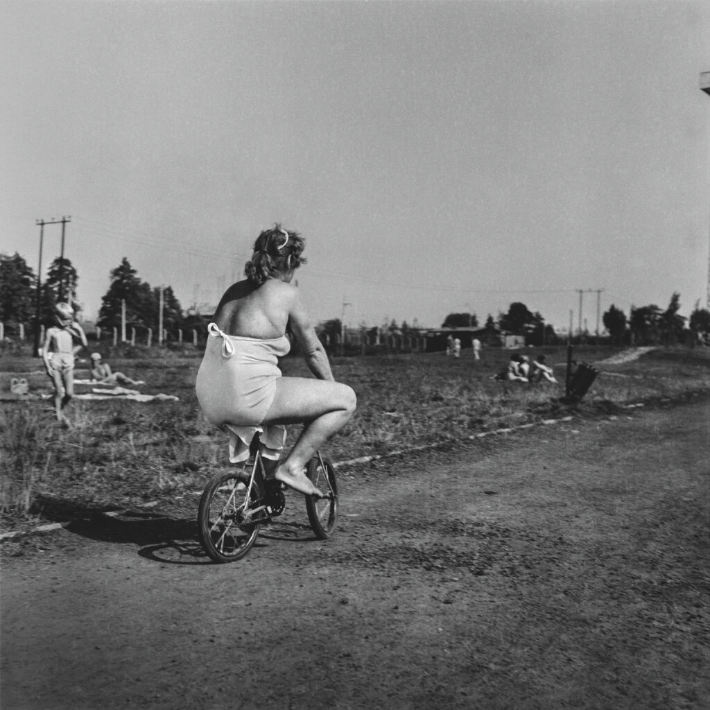 A woman in a beach suit is riding a child's bike.