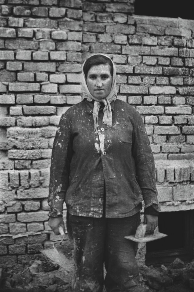 A woman in work clothes, with a trowel in her hand, poses for a photo against the background of a brick wall.