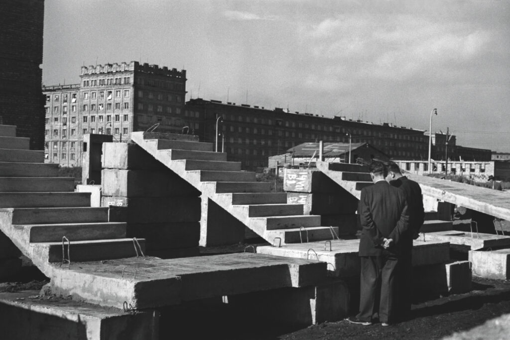 Two men in suits look at types of prefabricated stairs in public view. Residential buildings in the background.