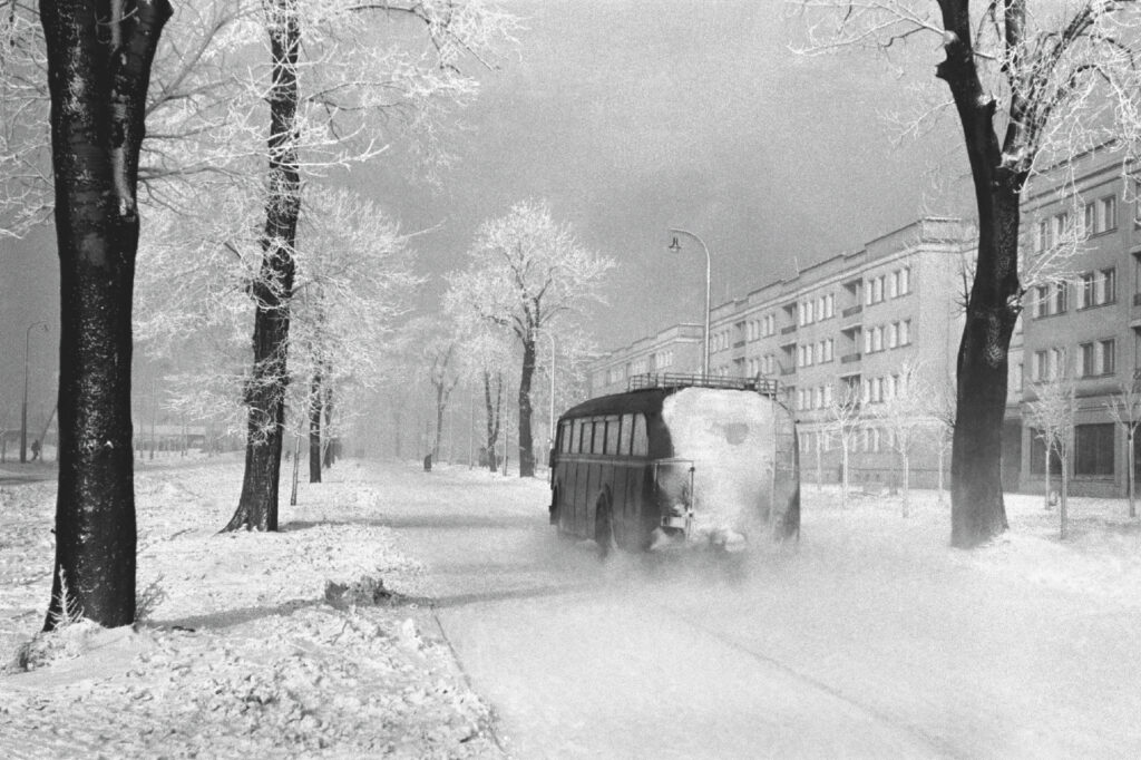 The bus goes through the snowy estate.