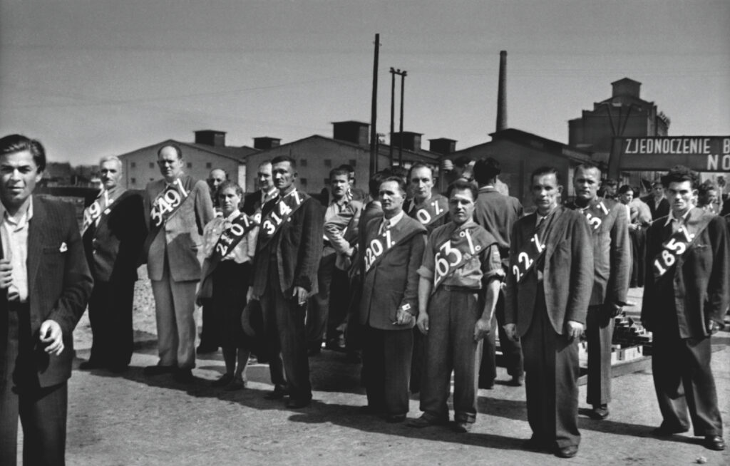 Men in suits, girdled with scarves with percentages above 100, stand in a row.
