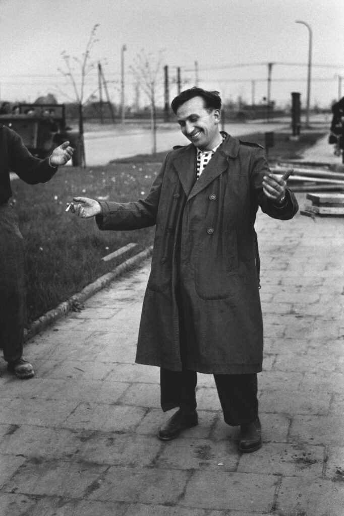 A man in a coat standing on the pavement spreads his hands wide, smiling at the same time. He is holding a cigarette in his right hand.