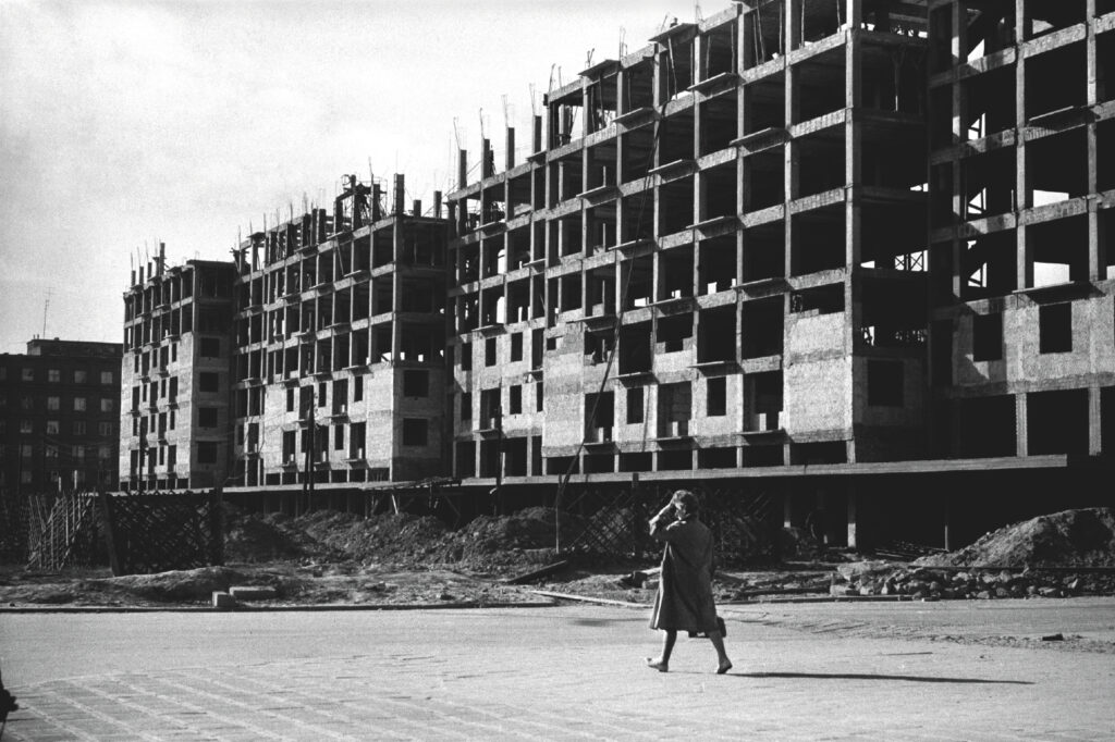 A woman in a coat walks dynamically, a long block under construction in the background.