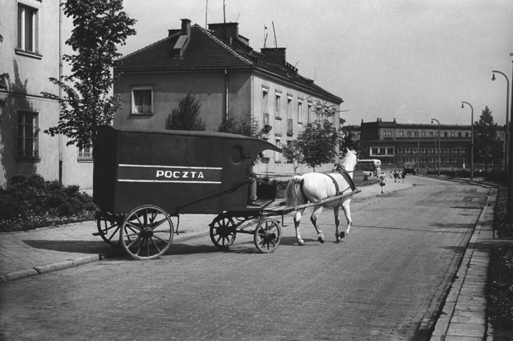 A postal coach drawn by a white horse drives from between the blocks to the street.
