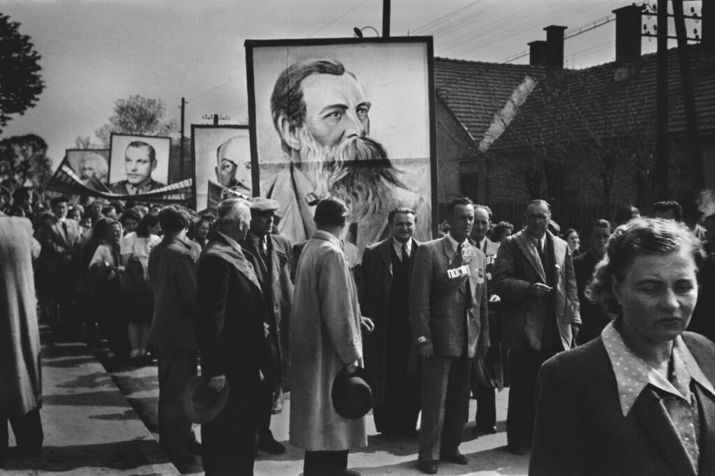 Men and women in cloaks march in the parade, above them enormous portraits of mustache and bearded men.