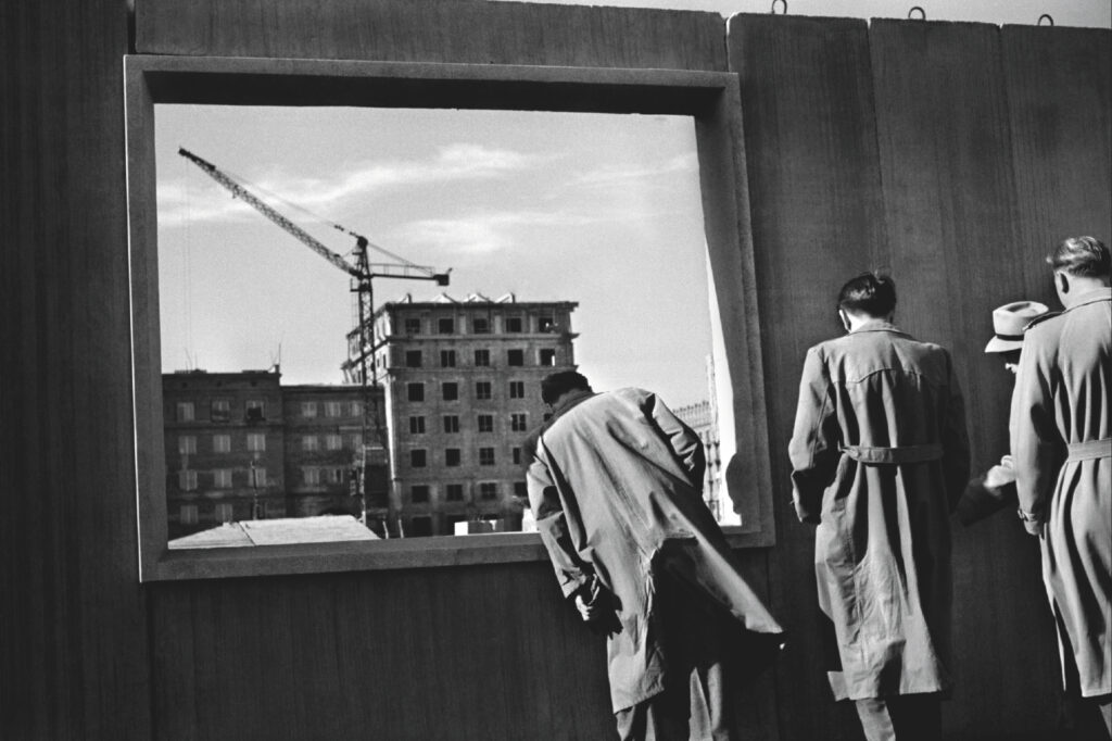 Men in coats look through a window opening in a prefabricated wall set at ground level. Residential buildings and a crane in the background.