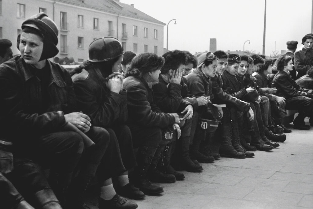 Women in competition uniforms sit on a long bench in the open air.