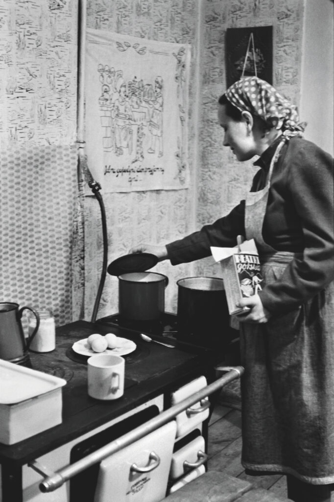 A woman with a swag on her head and a kitchen apron leans over the pots on the stove.