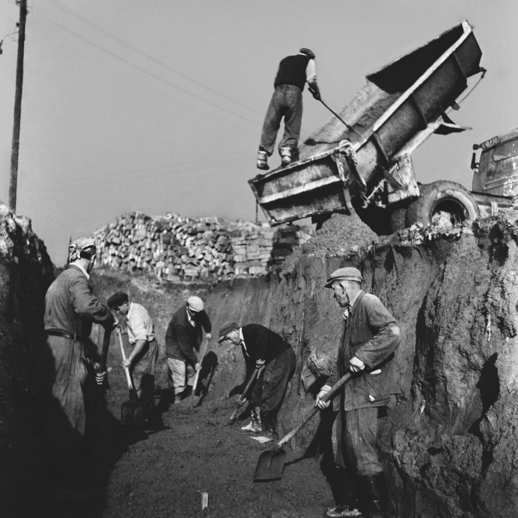 The men work in a deep trench, over them a truck with a tilted trailer.