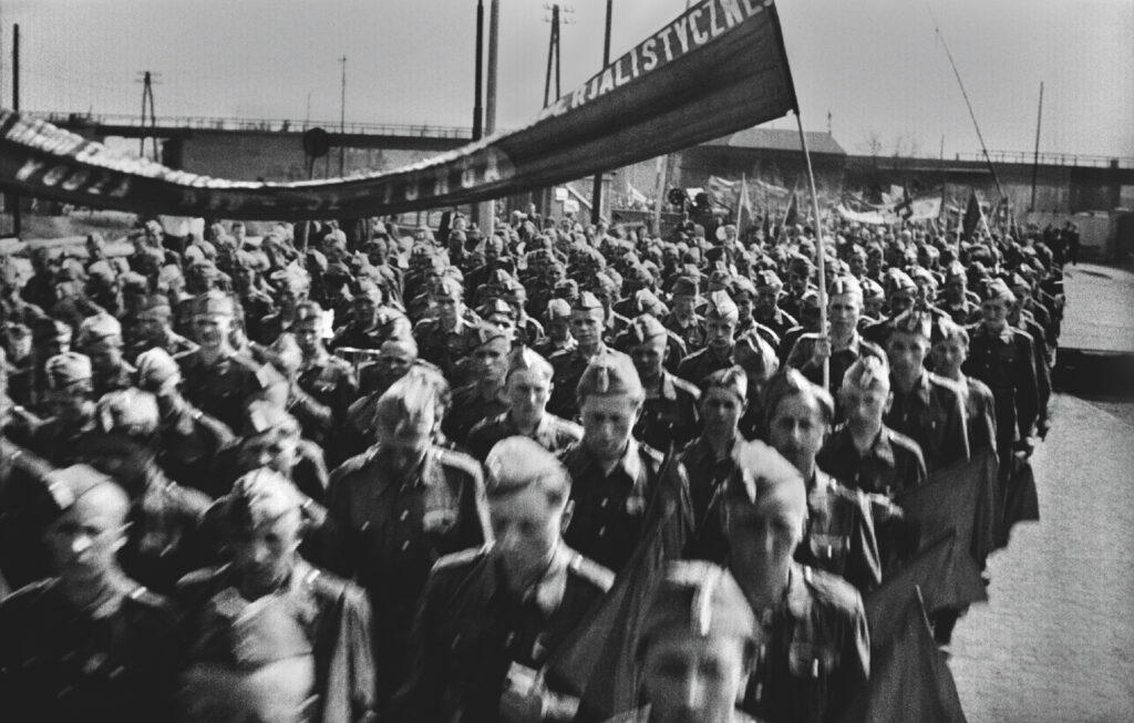 Volunteers in uniforms march dynamically in the procession. Above them, a banner with an illegible inscription.