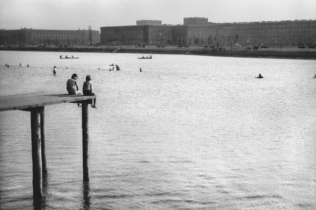 Two boys in swimming trunks are sitting on the edge of a wooden pier situated high above the lagoon water level. In the background, on the other side, there are residential buildings.