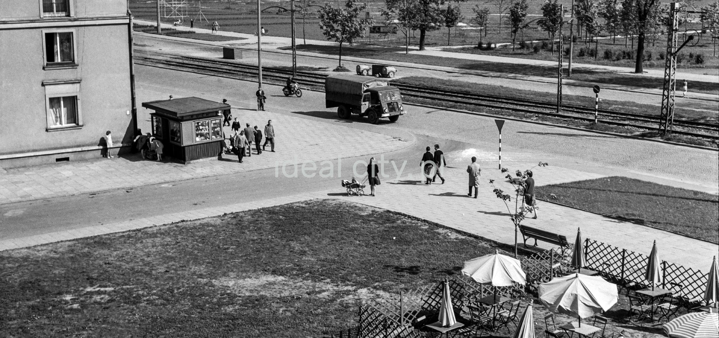 Ujęcie z okna ruch przed blokiem, widoczny kiosk ruch, parasole kawiarni, samochody, piesi na chodniku.